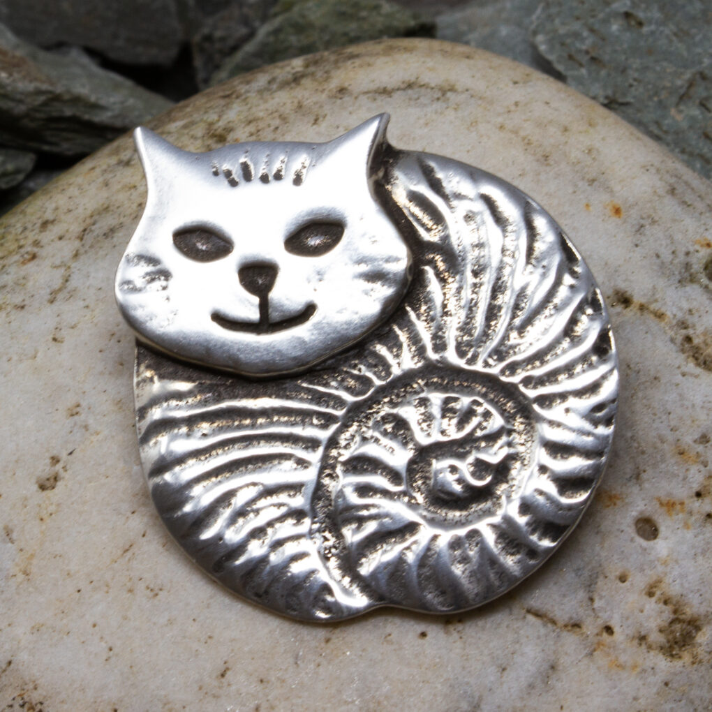 a fat cat brooch made of pewter