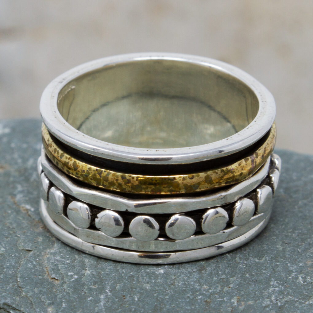 a silver and brass spinning ring with dots copy
