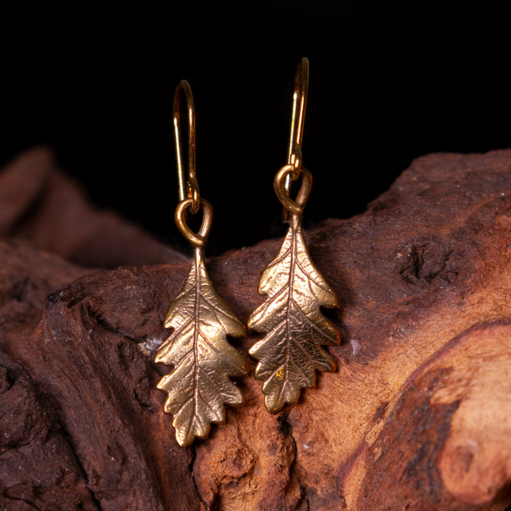 a pair of oak leaf earrings in bronze