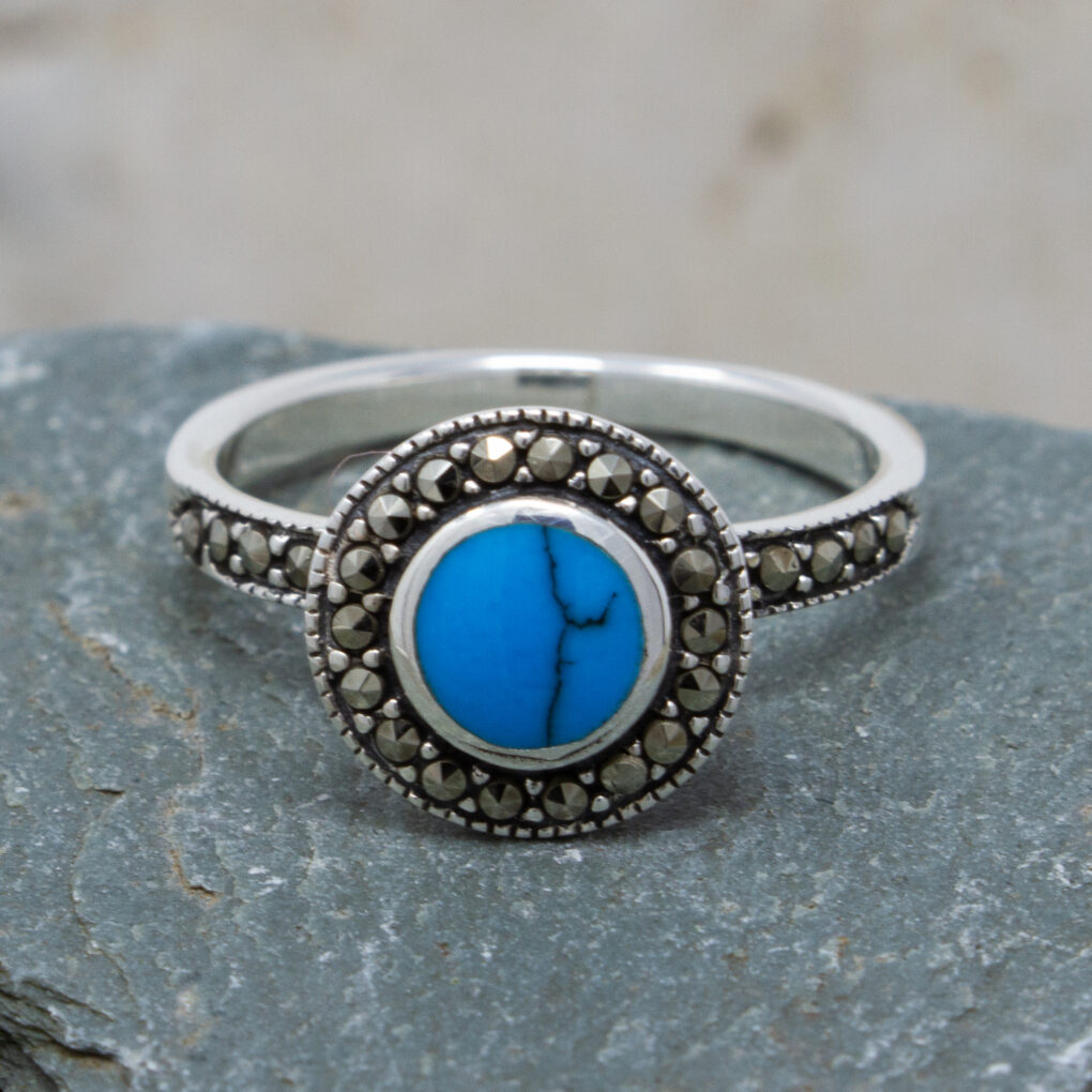 sterling silver ring with a raised turquoise gemstone surrounded by marcasite detail
